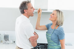 Happy woman feeding man in the kitchen Stock Images