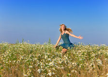 The happy Woman in the field  of camomiles.country landscape in a sunny day Royalty Free Stock Photography