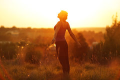 Happy woman in a field at sunset Stock Photography
