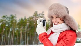 Happy woman with film camera over winter forest royalty free stock image