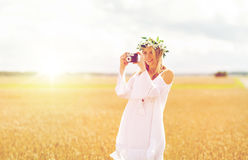 Happy woman with film camera in wreath of flowers Stock Photo