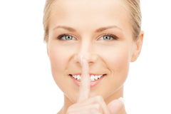Happy woman with finger on lips Royalty Free Stock Images