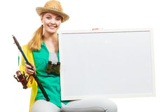 Happy woman with fishing rod holding board. Fishery, spinning equipment, angling sport and activity concept. Happy woman with fishing rod holding blank white stock photos