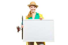 Happy woman with fishing rod holding board. Fishery, spinning equipment, angling sport and activity concept. Happy woman with fishing rod holding blank white stock images