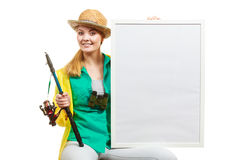 Happy woman with fishing rod holding board. Fishery, spinning equipment, angling sport and activity concept. Happy woman with fishing rod holding blank white stock photo