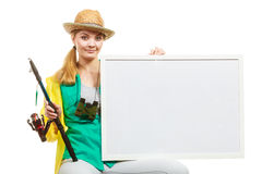 Happy woman with fishing rod holding board. Fishery, spinning equipment, angling sport and activity concept. Happy woman with fishing rod holding blank white stock photography