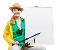 Happy woman with fishing rod holding board Stock Photography