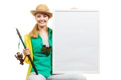 Happy woman with fishing rod holding board stock image