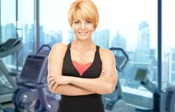 Happy woman fitness instructor over gym background Royalty Free Stock Photography