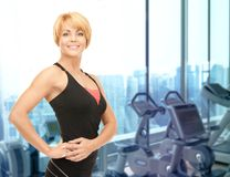 Happy woman fitness instructor over gym background Stock Photos