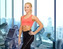 Happy woman fitness instructor over gym background Royalty Free Stock Images