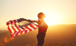 Happy woman with flag of united states enjoying the sunset on na Stock Images