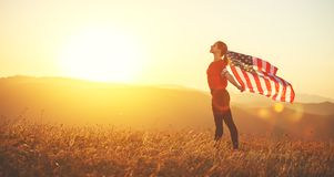 Happy woman with flag of united states enjoying the sunset on na. Young happy woman with flag of united states enjoying the sunset on nature royalty free stock images