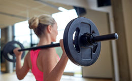 Happy woman flexing muscles with barbell in gym Royalty Free Stock Photo