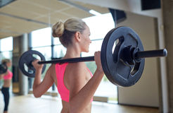Happy woman flexing muscles with barbell in gym. Fitness, sport, training, people and lifestyle concept - happy woman flexing muscles with barbell in gym Stock Photography