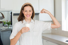 Happy woman flexing muscles while drinking water in kitchen Royalty Free Stock Photo