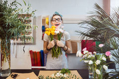 Happy woman florist with bunch of flowers standing and laughing Stock Photo