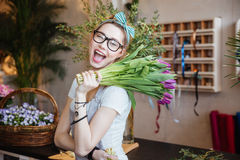 Happy woman florist holding bunch of purple tulips and winking Royalty Free Stock Photography