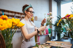 Happy woman florist holding flowers and making bouquet in shop Stock Images