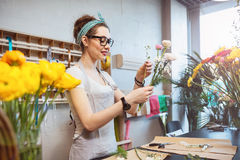 Happy woman florist holding flowers and making bouquet in shop Stock Photo