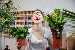 Happy woman florist holding plants in flowerpots and laughing Stock Photos