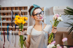 Happy woman florist holding white and yellow flowers in shop Stock Images