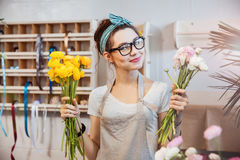 Happy woman florist holding white and yellow flowers in shop Royalty Free Stock Photos