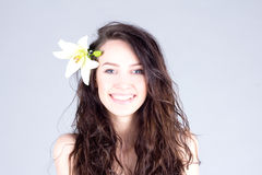 Happy woman with flower in curly hair with smile with teeth. SPA treatment. Stock Photography