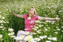 Happy woman in flower field Royalty Free Stock Image