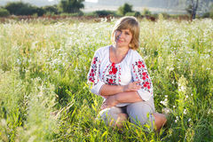Happy woman with flower relaxes in the grass with a flower. Royalty Free Stock Photos
