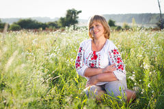 Happy woman with flower relaxes in the grass with a flower. Stock Photography