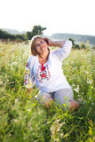 Happy woman with flower relaxes in the grass with a flower. Stock Image