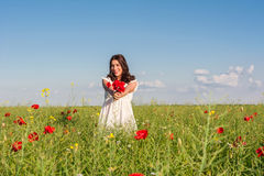 Happy woman in a flowering poppy field outdoors with a poppies bouquet Royalty Free Stock Photo