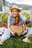 Happy woman with flowers having fun, enjoying picnic. Happy woman with basket of flowers having fun, enjoying picnic. Bicycle on background Stock Photography