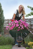 Happy woman with flowers in her garden Royalty Free Stock Image