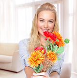 Happy woman with flowers at home Stock Images