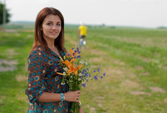 Happy woman with flowers in summer outdoors Stock Photography