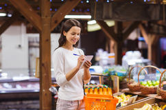 Happy woman with food basket and notepad in market Stock Photography