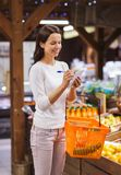 Happy woman with food basket and notepad in market Stock Photo