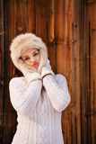 Happy woman fooling around with furry hat near rustic wood wall Royalty Free Stock Photography