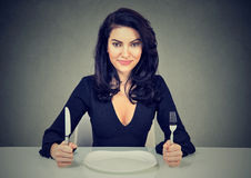 Happy woman with fork and knife sitting at table with empty plate Stock Photos