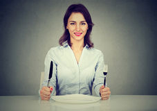 Happy woman with fork and knife sitting at table with empty plate Royalty Free Stock Photos