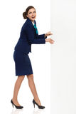 Happy Woman In Formalwear Pulling Big Banner. Young woman in blue formalwear and high heels pulling white banner and looking away. SIde view. Full length studio Royalty Free Stock Photos