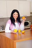 Happy woman with fresh orange juice. Holding oranges in kitchen Stock Photography