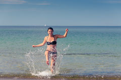 Happy woman frolicking on a tropical beach Stock Images