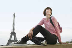 Happy Woman In Front Of Eiffel Tower. Happy young women sitting on balcony in front of Eiffel Tower Royalty Free Stock Image