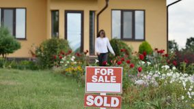 Happy woman in front of their new house.  stock footage