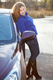 Happy woman in full length leaned against car Stock Photography