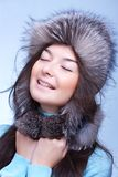 Happy woman in fur cap. On the blue background Stock Photos