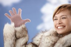 Happy woman in fur coat showing gloved hand Royalty Free Stock Photography